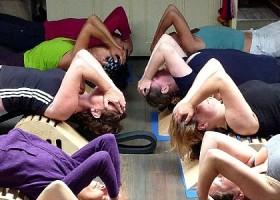 Yoga-Lab-Amsterdam-zes-mensen-liggen-achterovergebogen-op-bankje--in-yogahouding-met-handen-op-voorhoofd Wereld van Yoga