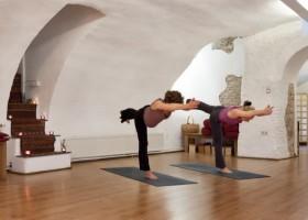 Yoga-Utrecht-twee-vrouwen-beoefenen-staande-yogahouding-met-armen-naar-voren-gericht-en-staand-op-blauwe-yogamat-in-witte-ruimte Wereld van Yoga