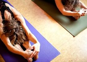 Svaha-Yoga-Amsterdam-twee-mensen-doen-voorovergebogen-yogahouding-op-een-yogamat-met-zonnestralen-op-hun-hoofd Wereld van Yoga