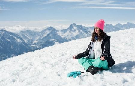 yoga in de sneeuw vrouw zit op berg