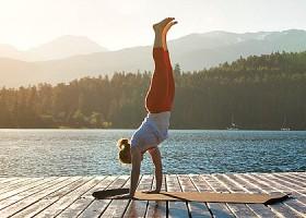 Yoga-Point-Utrecht-Oudegracht-vrouw-doet-handstand-op-matje-op-steiger-aan-een-meer Wereld van Yoga