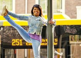 Yoga-Moves-Utrecht-vrouw-in-spijkerkleding-staat-op-hek-in-de-stad-en-doet-yogahouding Wereld van Yoga