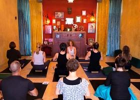 Svaha-Yoga-Amsterdam-achte-mensen-zitten-op-kussentje-en-volgen-yogales-van-vrouw-in-studio-met-gekleurde-muren-en-gordijnen Wereld van Yoga