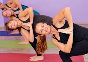 Kompassie-Yoga-Rotterdam-Delfshaven-Wereld-van-Yoga-4-vrouwen-doen-buigende-yogahouding-op-gekleurde-matjes Wereld van Yoga
