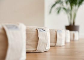 Yoga-Spot-Amsterdam-vrijf-beige-meditatiekussentjes-op-een-houten-vloer-met-een-plant Wereld van Yoga
