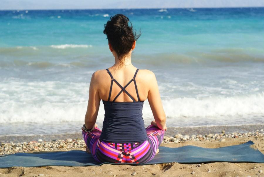 reis yogamat vakantie vrouw op strand met mat Welke reis yogamat voor de vakantie? - Wereld van Yoga