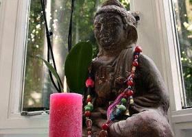 Yoga-Lab-Amsterdam-boeddha-beeld-met-roze-kaars-en-bloem-voor-het-raam Wereld van Yoga