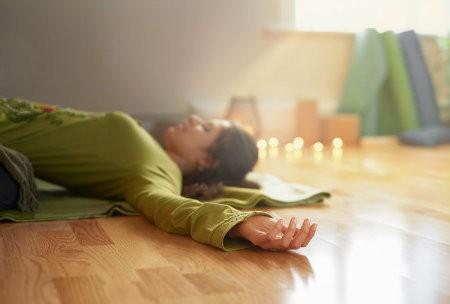 verschil restorative yoga nidra vrouw ligt props