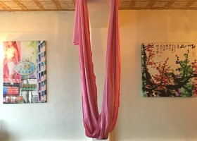 wat is aerial yoga roze doek aan plafond yogazaal Wat is Aerial Yoga? Ik probeer het uit! - Wereld van Yoga