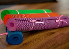 Yoga-Point-Utrecht-vier-gekleurde-yogamatten-met-touwtje-eromheen-op-houten-vloer Wereld van Yoga