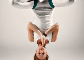 Kompassie-Yoga-Rotterdam-Delfshaven-Aerial-Yoga-vrouw-doet-ondersteboven-yogahouding-in-hangmat Wereld van Yoga