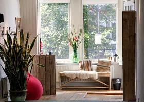 Yoga-Point-Utrecht-Oudegracht-relaxhoekje-met-houten-bankje-met-schapenvel-en-plant-en-kussentjes-voor-het-raam Wereld van Yoga