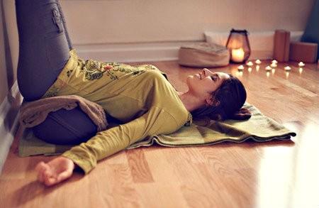 wat is restorative yoga vrouw liggend yogahouding tegen muur