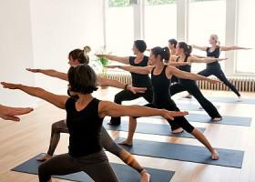 Yoga-Spot-Amsterdam-zeven-vrouwen-in-zwarte-kleding-doen-staande-yogahouding-op-blauwe-matten Wereld van Yoga