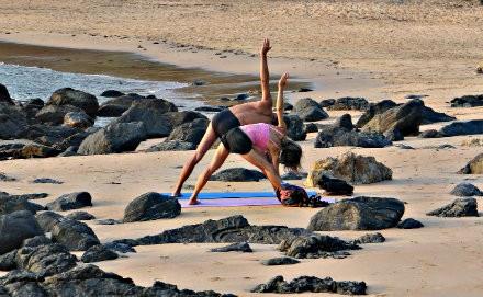 4 tips yoga volhouden vakantie samen yoga doen op strand