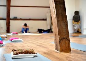 yoga studio saktiisha den haag centrum zaal met houten vloer balken yogamatjes Wereld van Yoga