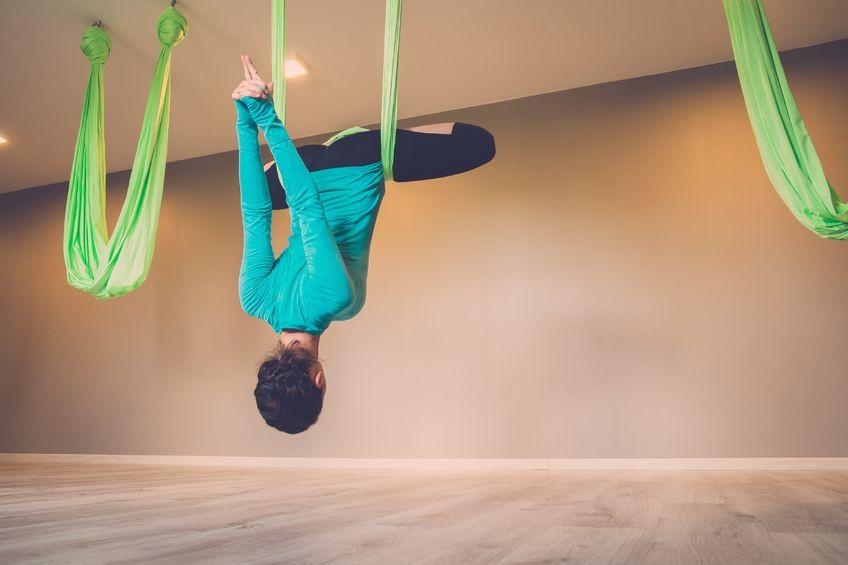 Wat-is-Aerial-Yoga-Wereld-van-Yoga-vrouw-hangt-in-doek-in-yogazaal Wat is Aerial Yoga? - Wereld van Yoga